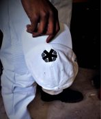 right hand holding a white baseball cap